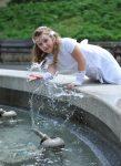 w białej komunijnej sukience przy fontannie chlapie