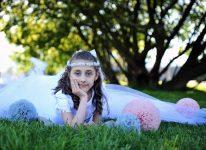 w białej komunijnej sukience na trawie