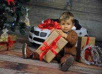 mały z prezentem pod choinką w tle BMW ma chłopak szczęście i bogatego mikołaja